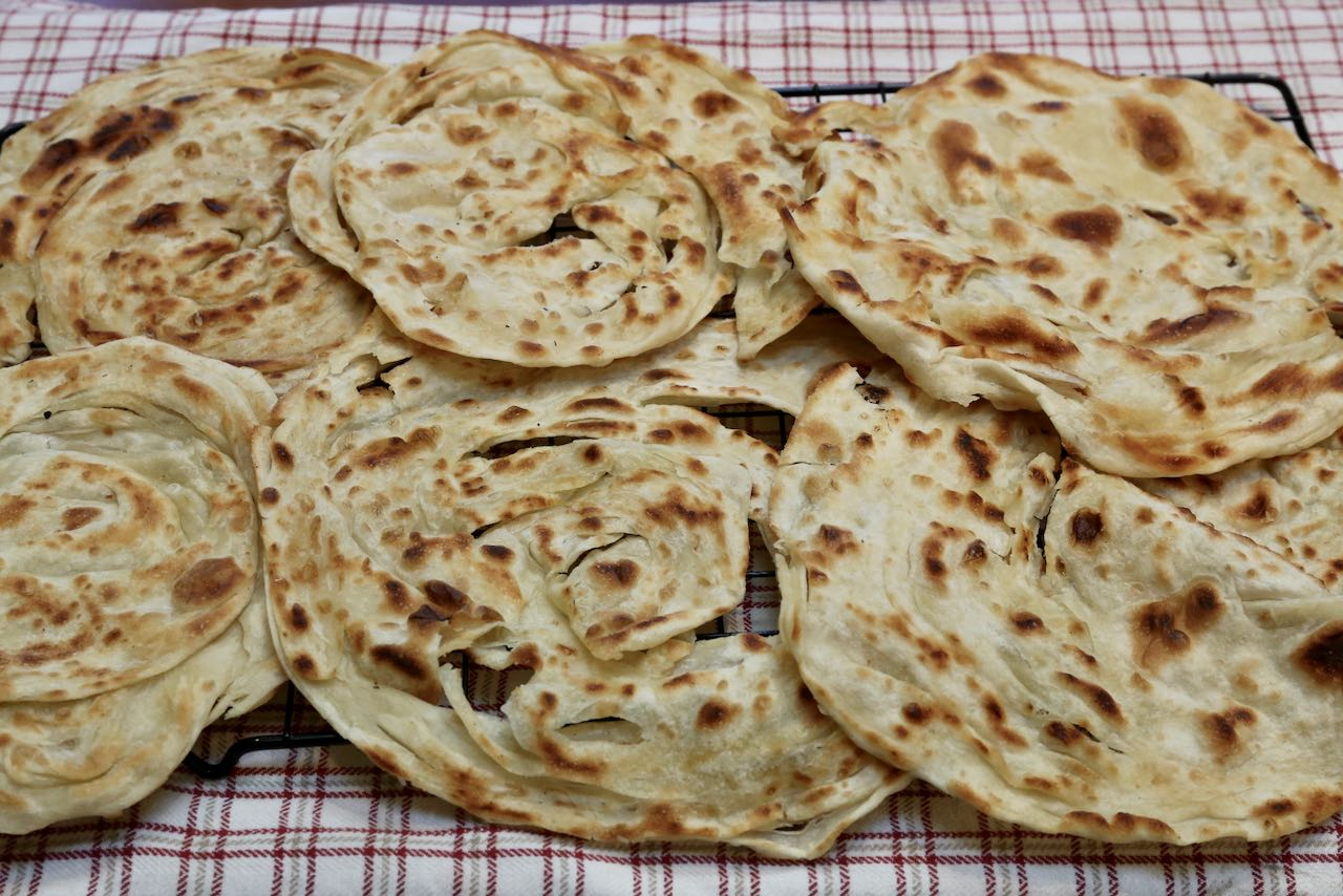 Cool crispy and flaky roti canai flatbread on a rack before serving.