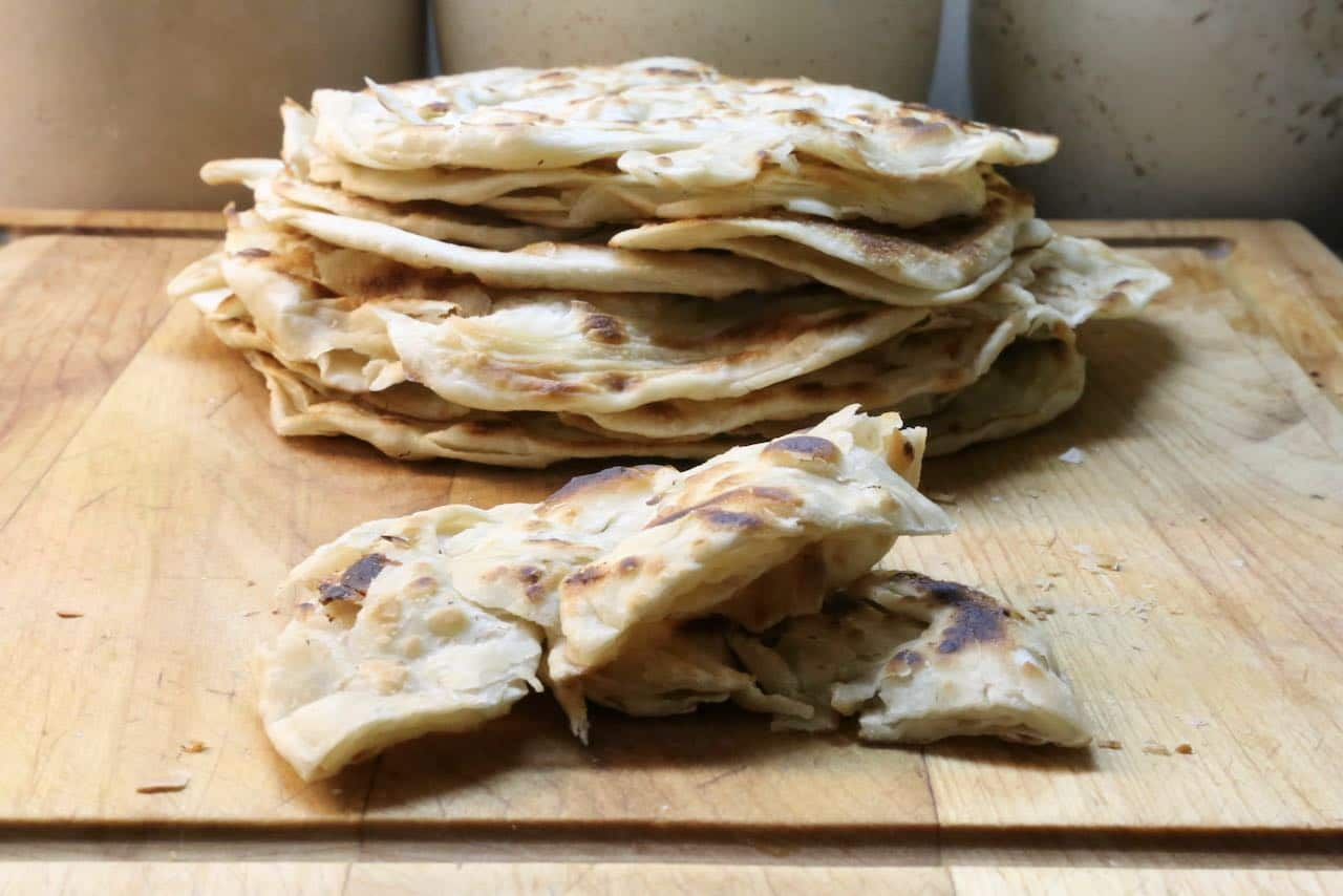 Roti canai is a flaky and crunchy flatbread from Malaysia served with curry sauce.