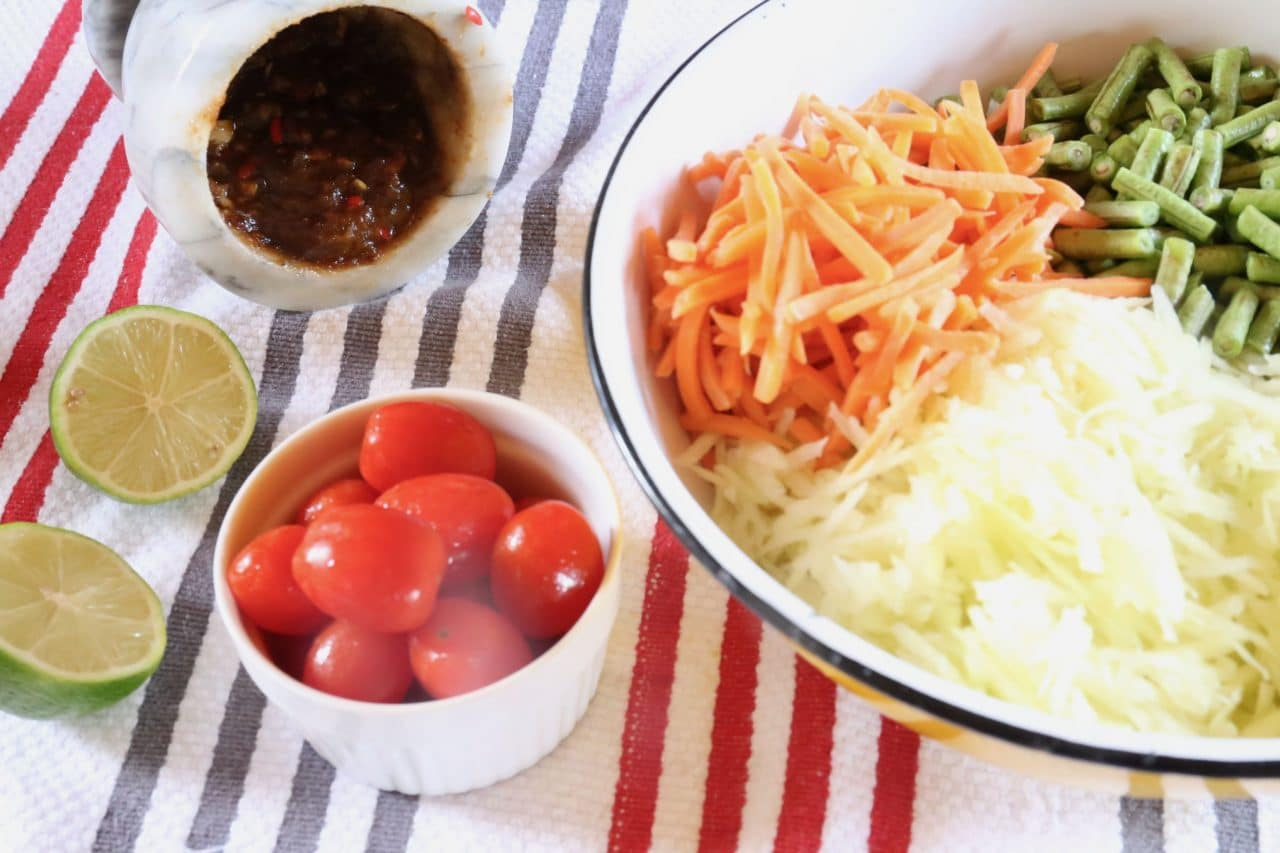 Combine vegetables with Laos Papaya Salad paste in a large mixing bowl with lime juice.