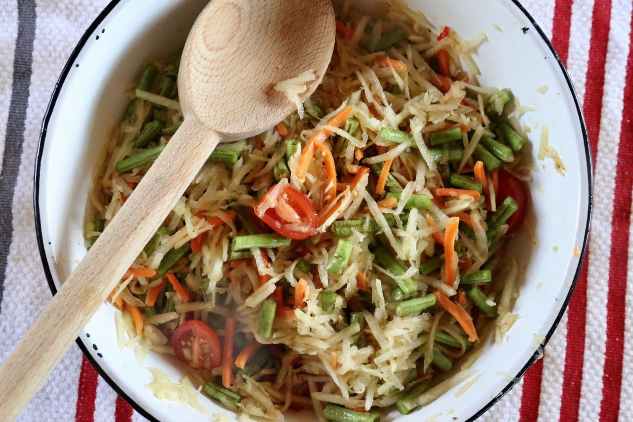 Stir Lao Papaya Salad ingredients with a wooden spoon in a large mixing bowl until fully combined.