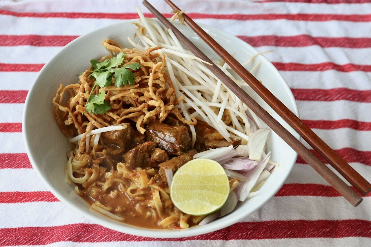 Serve Chiang Mai Noodles in a large soup bowl with chopsticks.