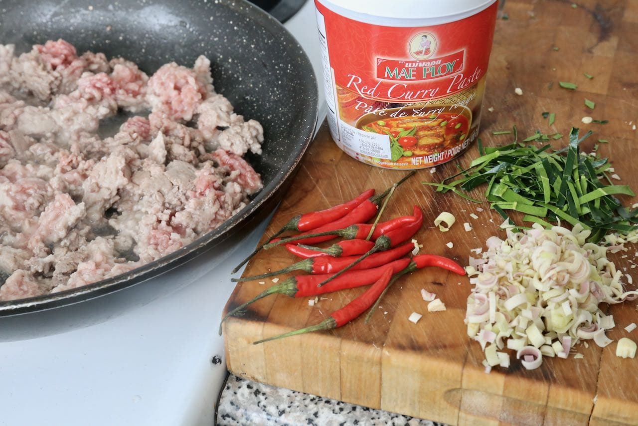Fry pork and beef mince curry while chopping hot peppers, lemongrass and kaffir lime leaf.