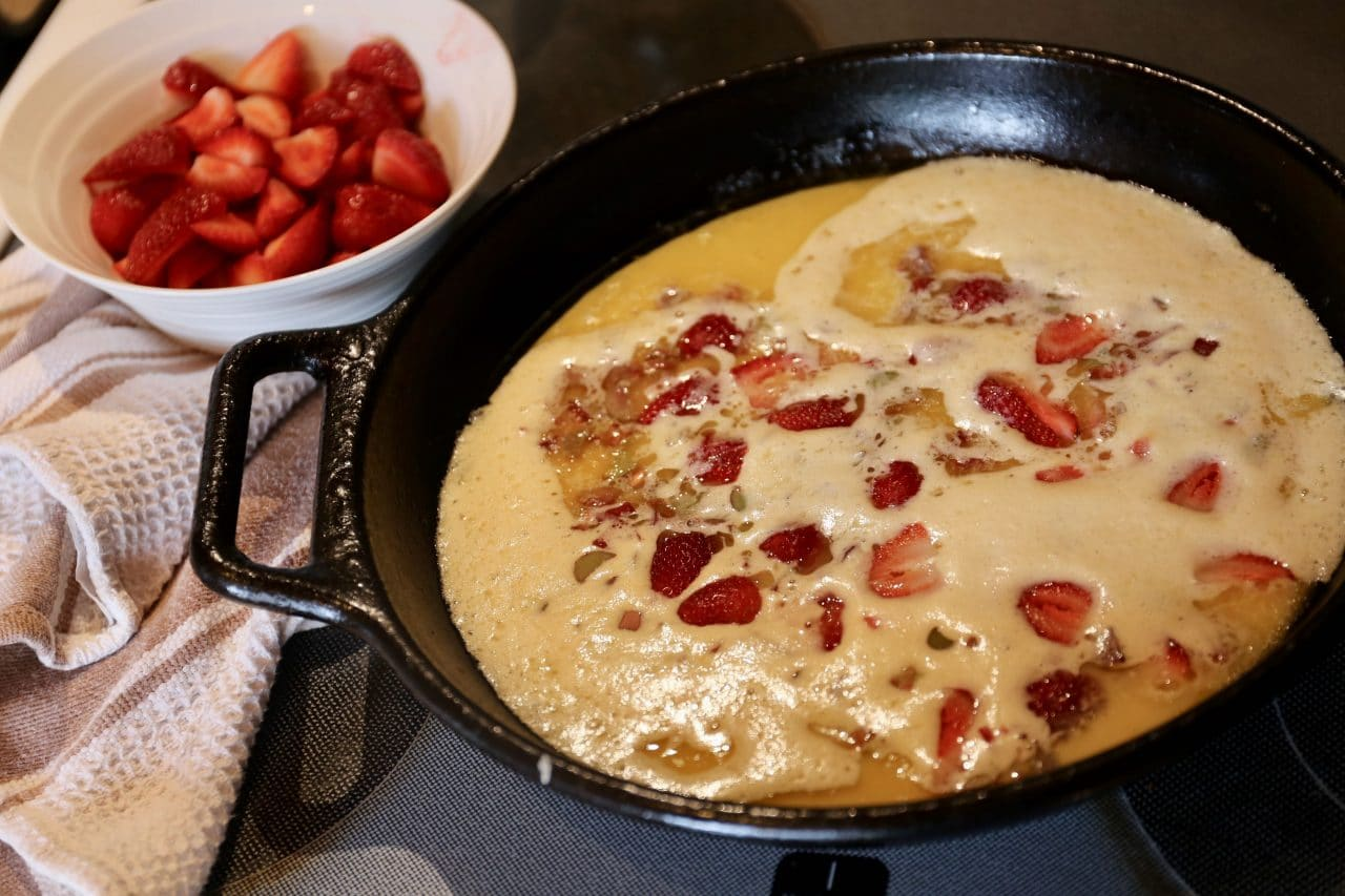 Top Dutch Baby batter with sliced strawberry and rhubarb.