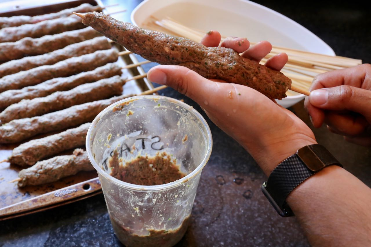 Use wet hands to form Afghan kebabs on water soaked wooden skewers.