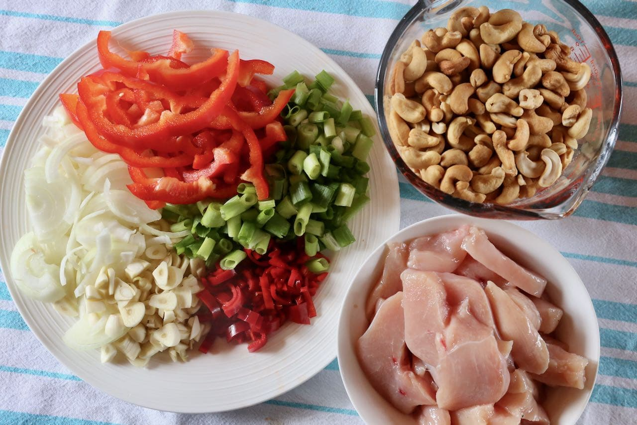 Prep Gai Pad Med Mamuang ingredients featuring sliced chicken, red pepper, scallions, onion, garlic and chili.