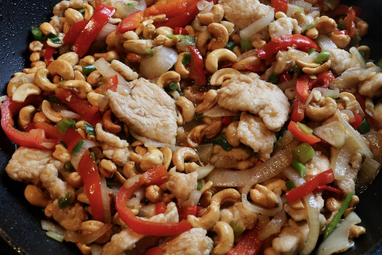Thai Cashew Chicken features sliced chicken breast, onions, red pepper and roasted cashews.