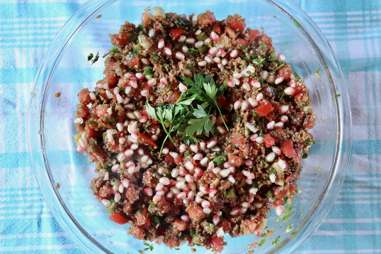 Top Turkish Kisir with pomegranate seeds and parsley.
