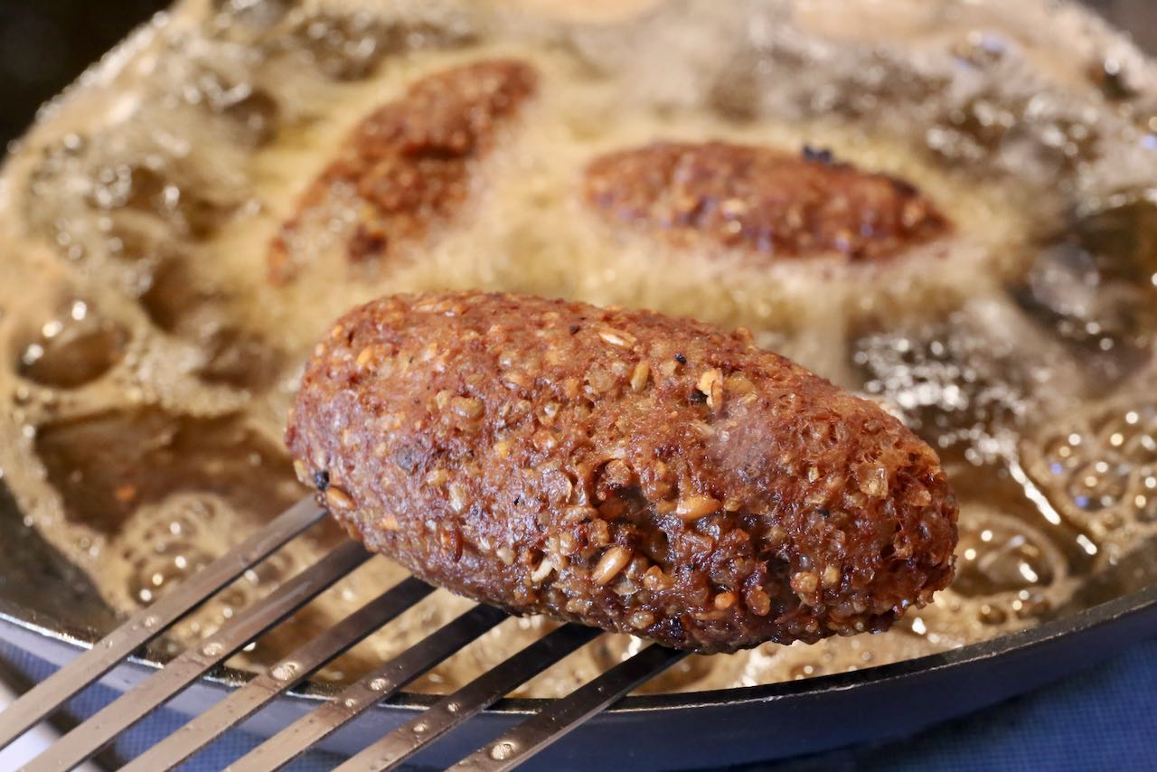 Remove fried kibbeh from bubbling oil using metal tongs or flipper.