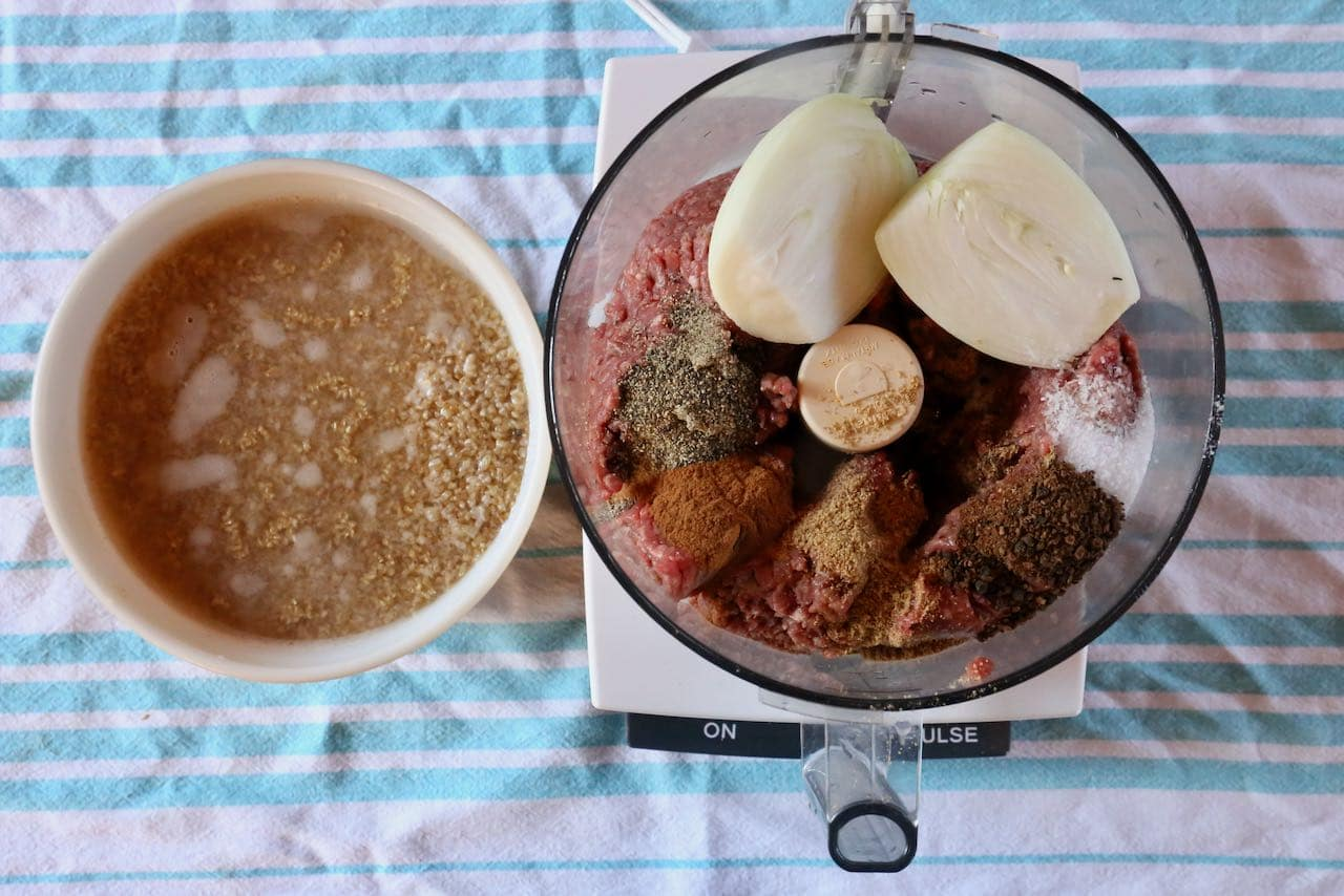 Prepare Lebanese Kibbeh casing by soaking bulgur in water and blending minced meat, onions and spices in a food processor.