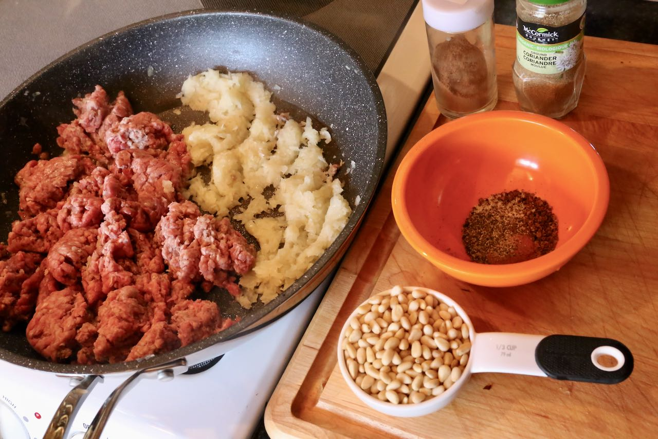 Prepare Lebanese Kibbeh filling by frying minced beef, onions, spices and pine nuts in a skillet.