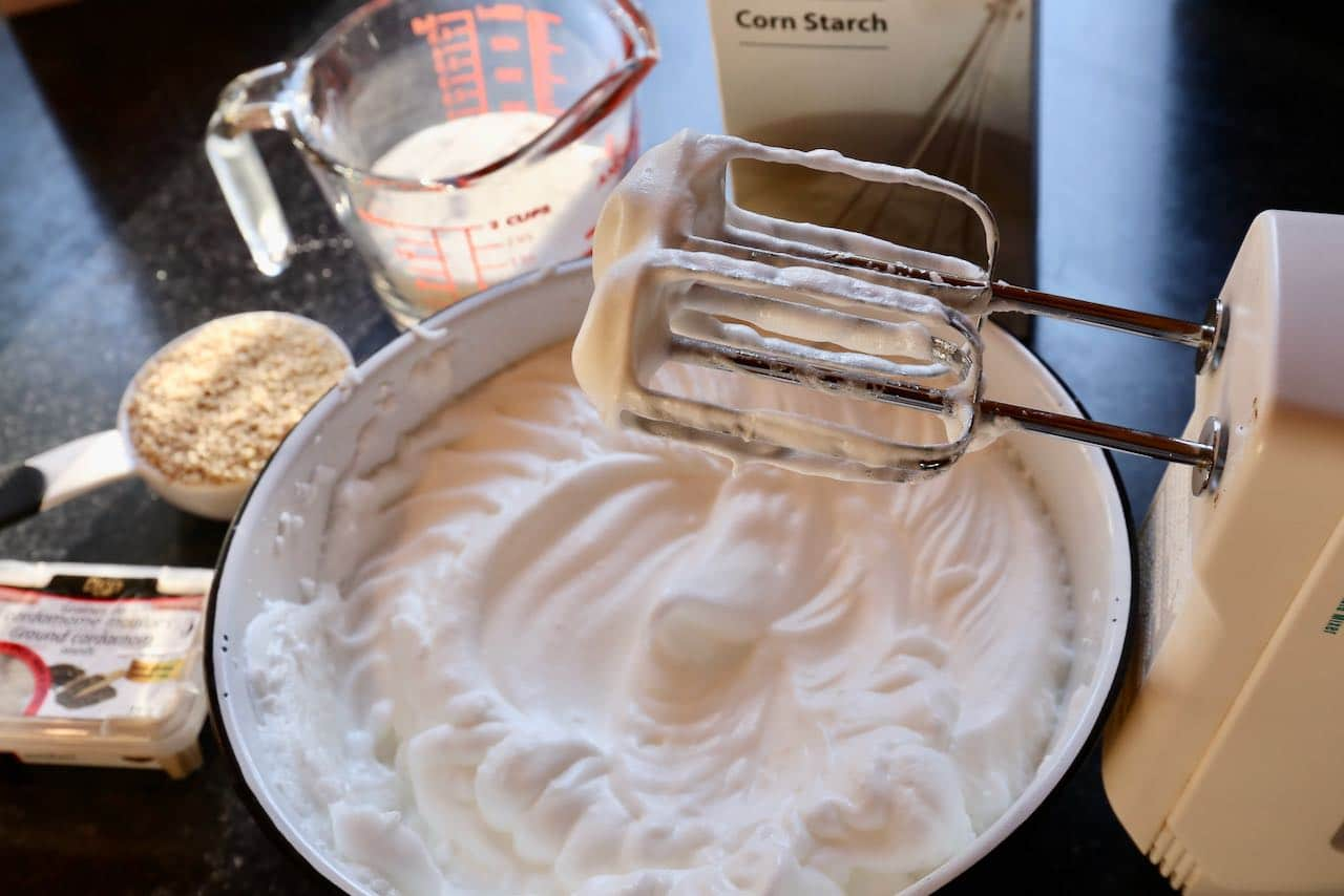 Begin making Jordgubbstårta by using egg beaters to whip meringue.
