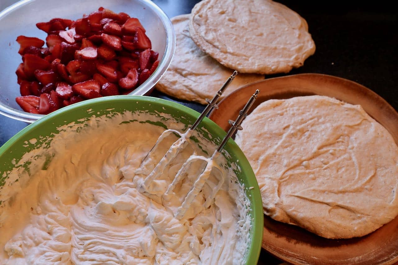 Assemble Jordgubbstårta by layering meringue, whipped cream and strawberries.