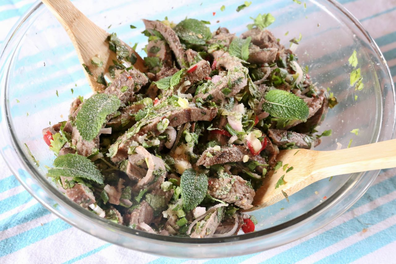 Toss cold Nam Tok Thai beef Salad and let marinate in the fridge before serving.