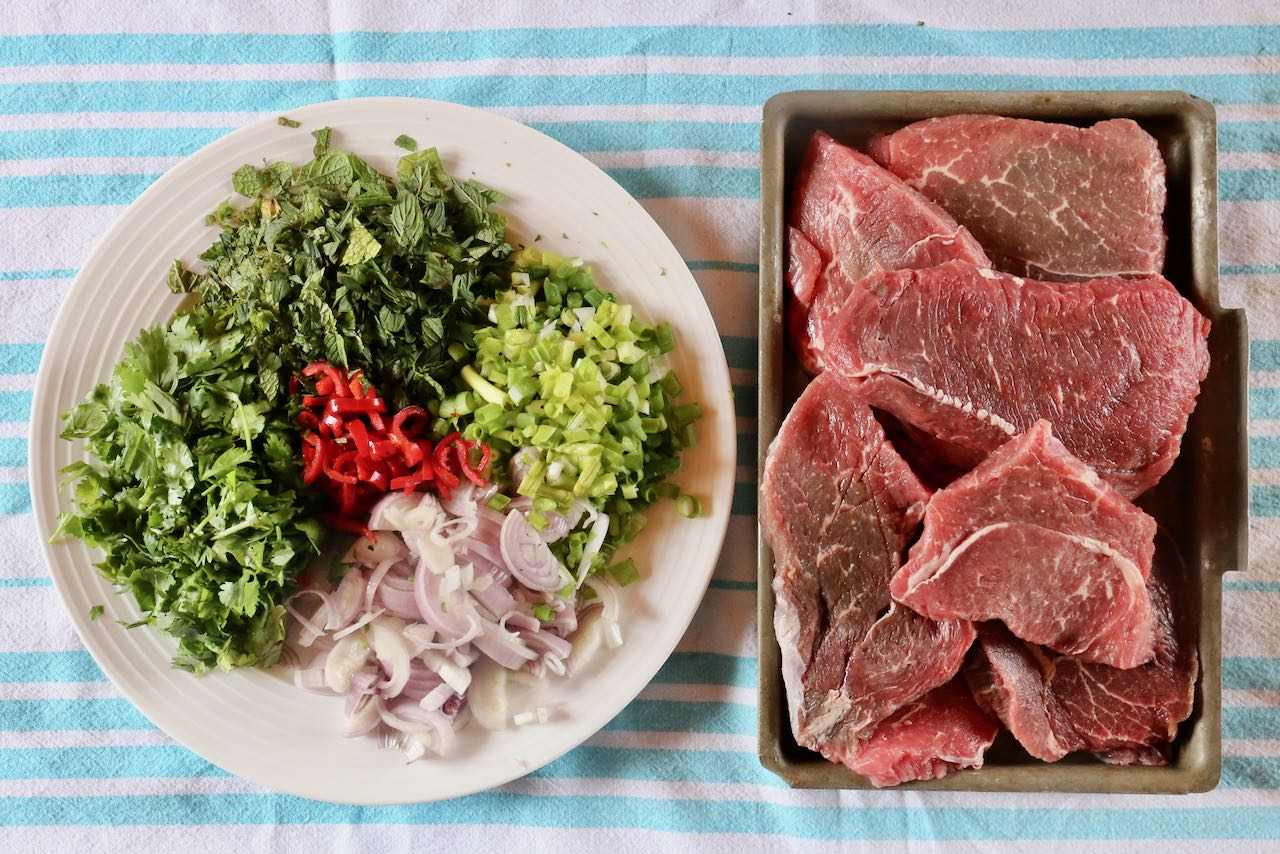 Nam Tok is a Thai Beef Salad featuring steak, mint, cilantro, scallion, shallot and spicy red chili.