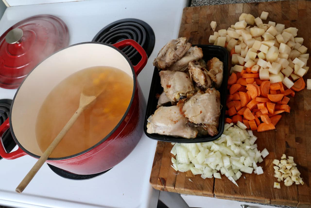 Add chicken thighs, broth, and vegetables to a large pot and simmer.