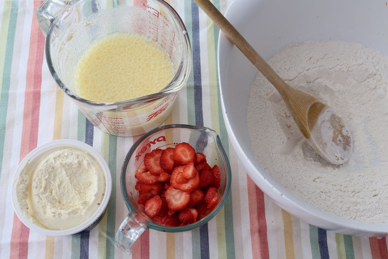 Slice strawberries, beat together wet ingredients and sift dry ingredients in a mixing bowl.