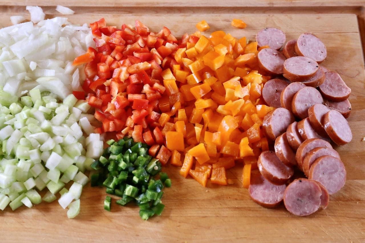 Begin preparing Cajun Shrimp Chowder by chopping vegetables and slicing sausage.