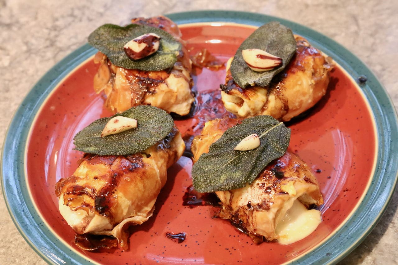Serve Involtini di Pollo with crispy sage, red wine reduction sauce and garlic.