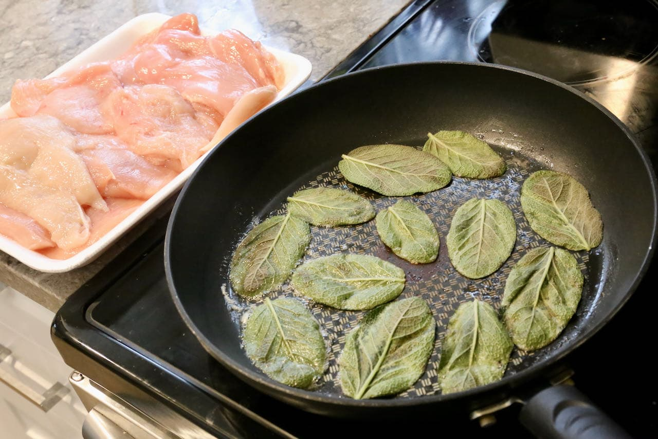 Begin preparing Involtini di Pollo by frying sage in butter until crispy.