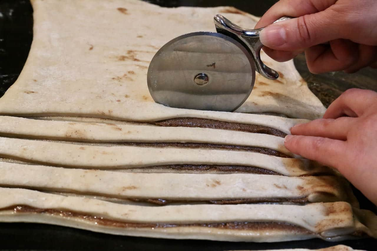 Use a pizza cutter to slice strips of Kardemummabullar dough.