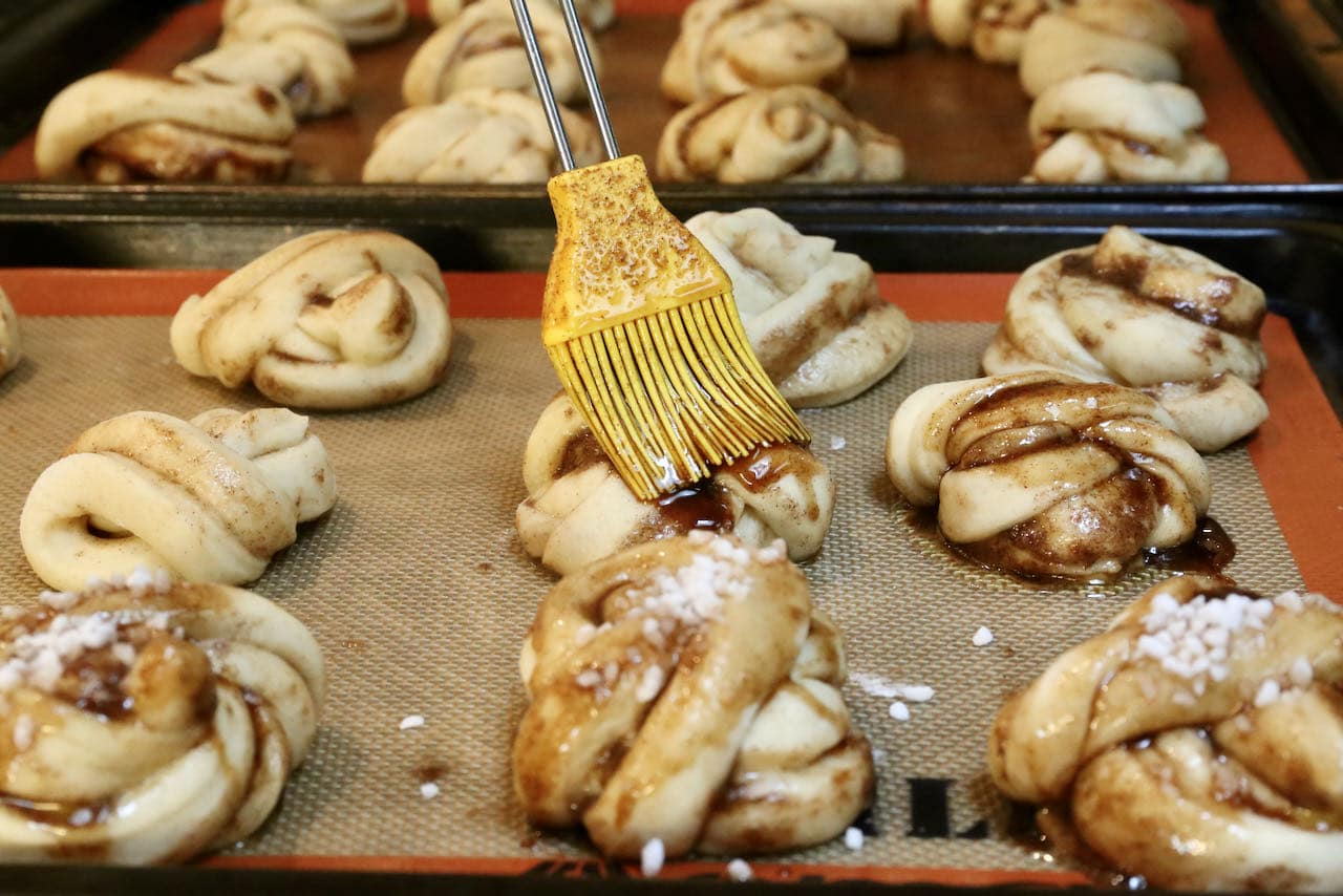 Use a pastry brush to slather Kardemummabullar with cinnamon cardamom glaze.