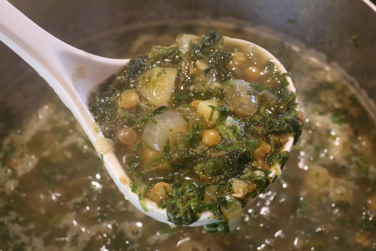 Use a ladle to serve healthy Adas Bil Hamod Lebanese Lentil Soup in bowls.