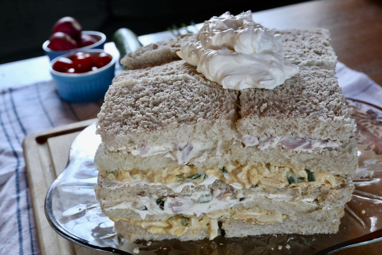 Once the Smorgastarta layers are complete top with savoury icing and spread across the top and sides of the Swedish Sandwich Cake.