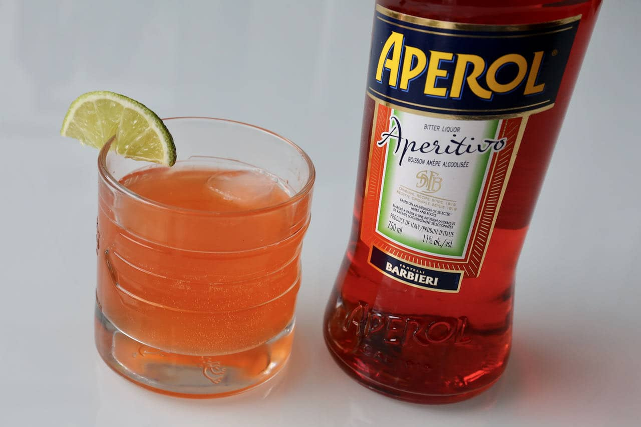 Aperol Gin Cocktail served in a rocks glass with a wedge of lime. A thirst quenching Italian summer tradition!