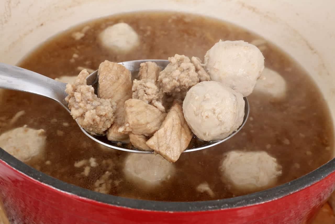 Cook pork balls, minced pork and sliced pork loin in flavoured soup broth.