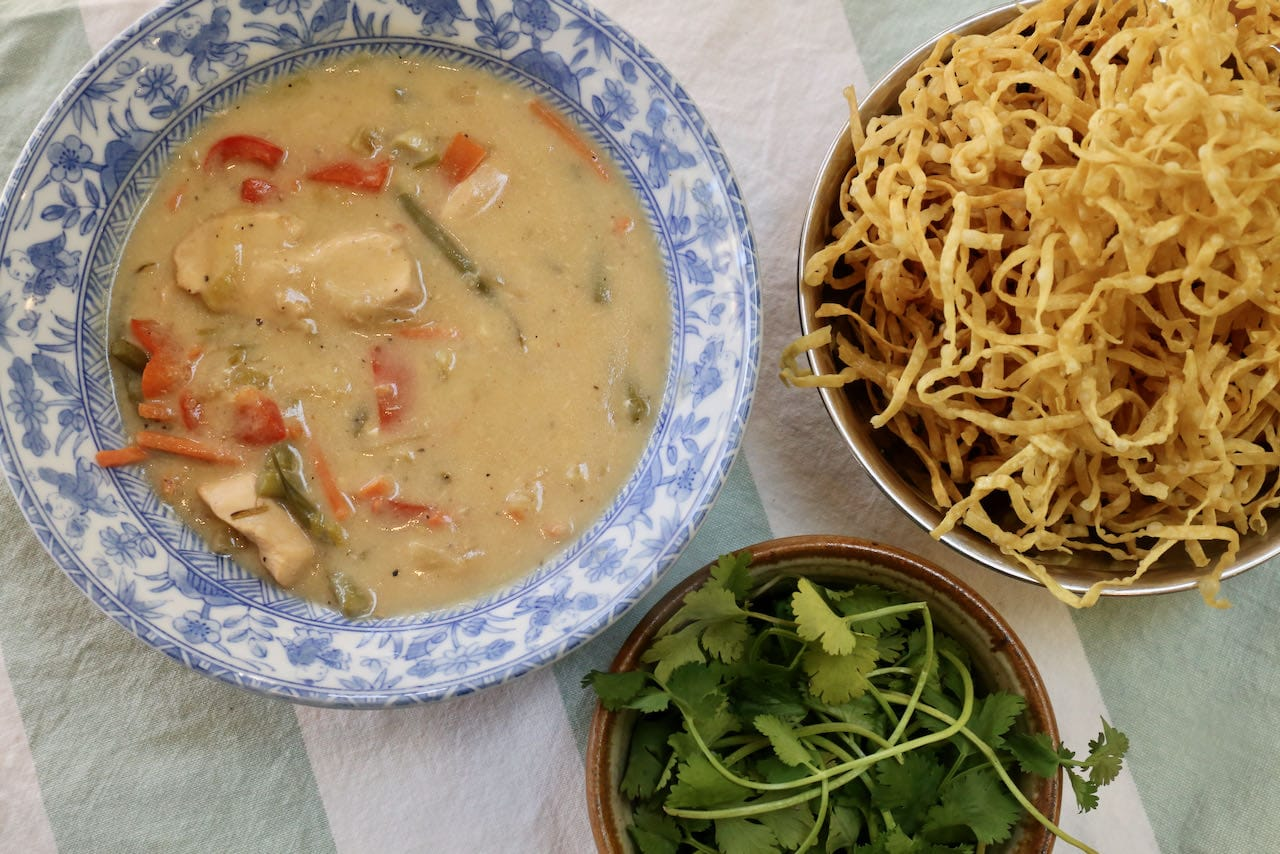 Assemble Chicken Manchow Soup by topping with fried egg noodles and cilantro.