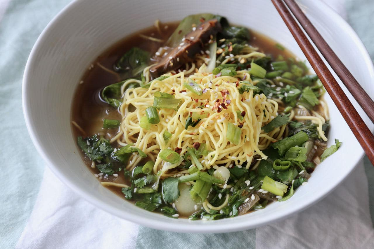 Chinese Ginger Garlic Soup is garnished with chili flakes, sesame seeds and scallions.