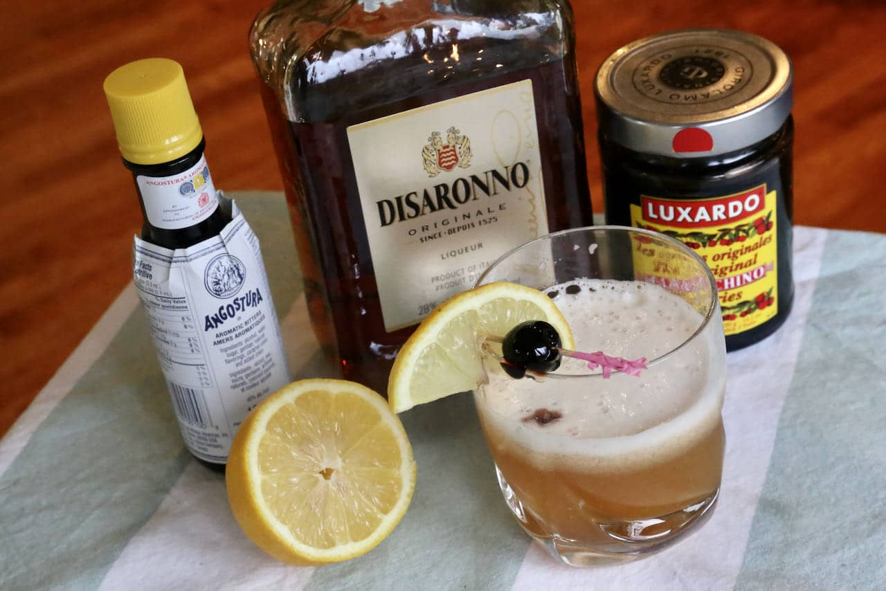Traditional Disaronno Sour cocktails feature amaretto, lemon juice, bitters, egg white and Maraschino cherries.