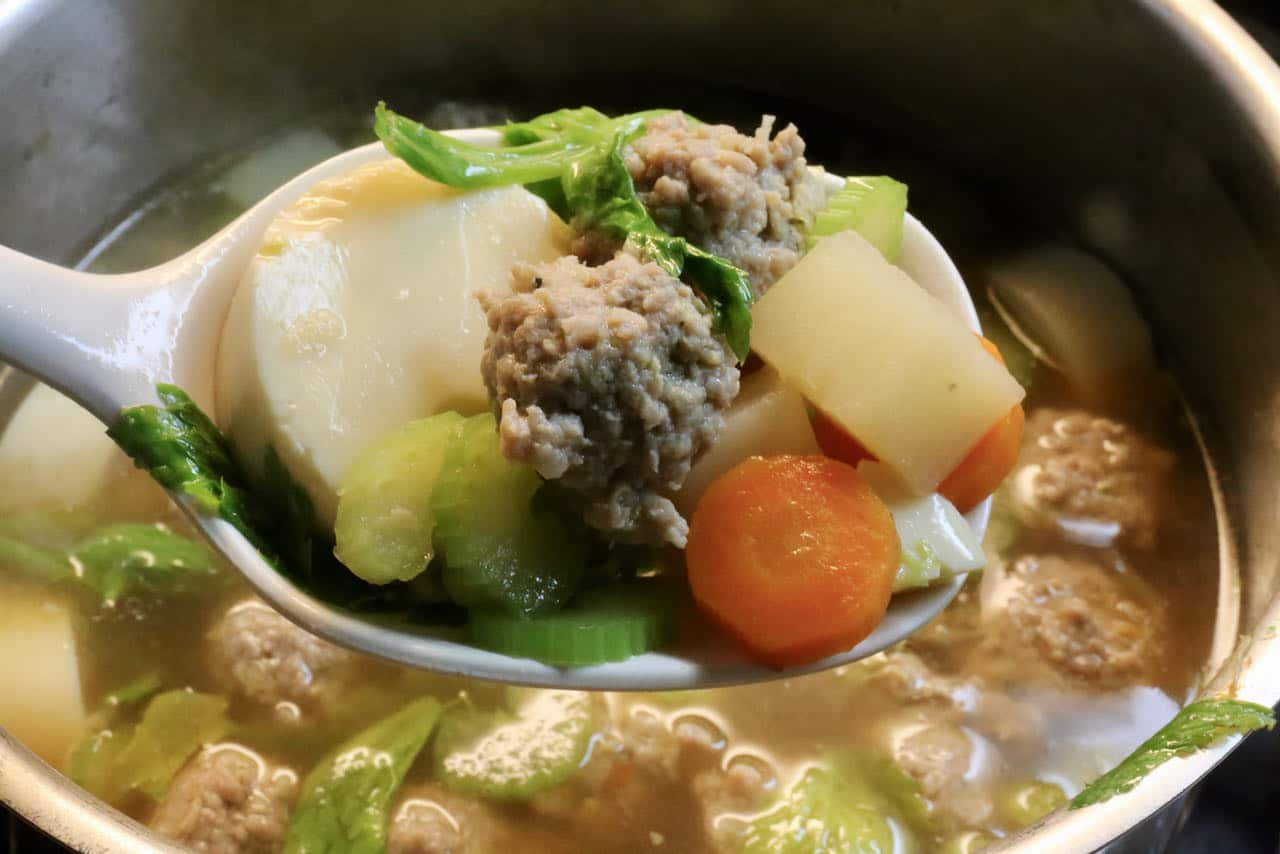 Traditional Egg Tofu Soup features tender vegetables, Thai herbs and tiny meatballs.