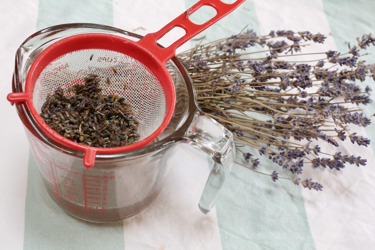 Prepare homemade lavender simple syrup then strain the liquid through a sieve.