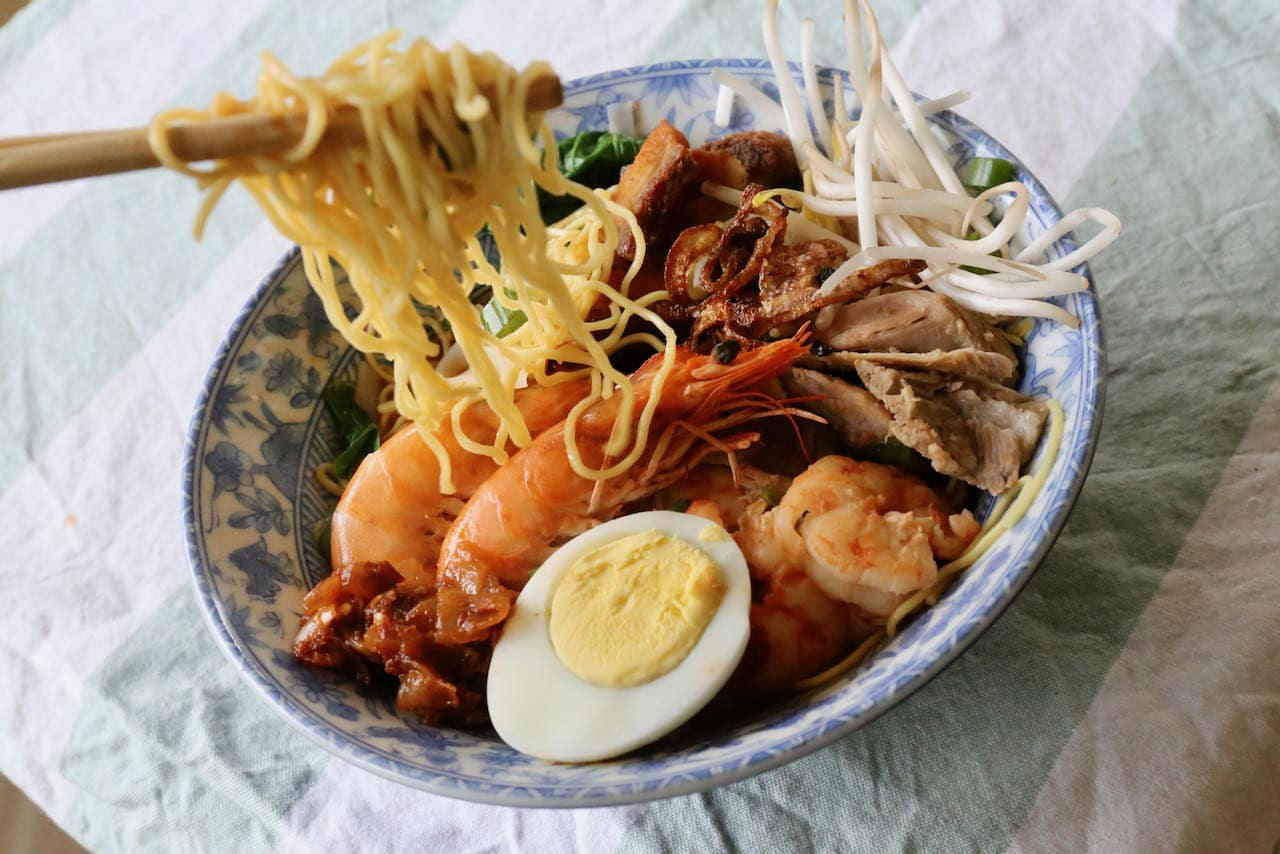 Eat Hokkien Mee Penang Prawn Noodle Soup with chopsticks.