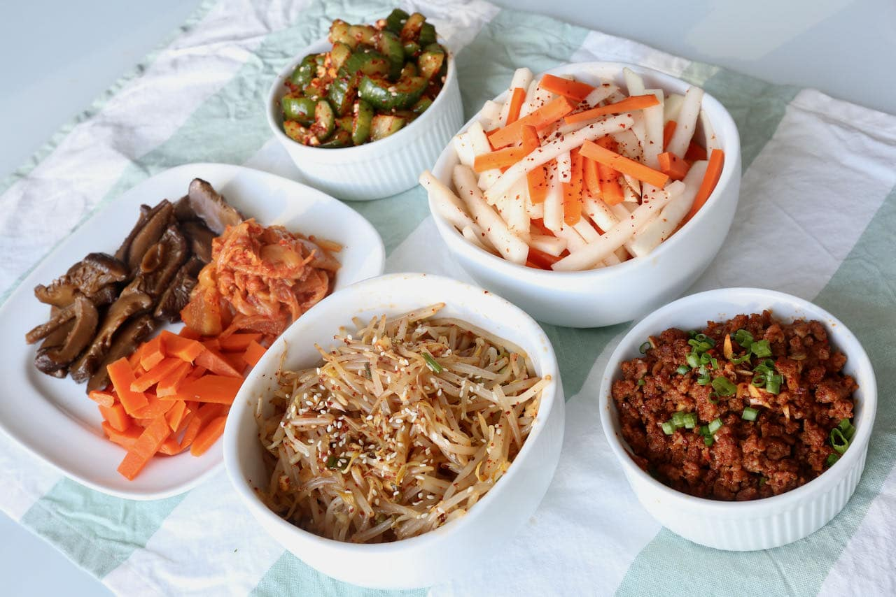 Spicy Pork Bibimbap is topped with a selection of healthy Korean banchan.
