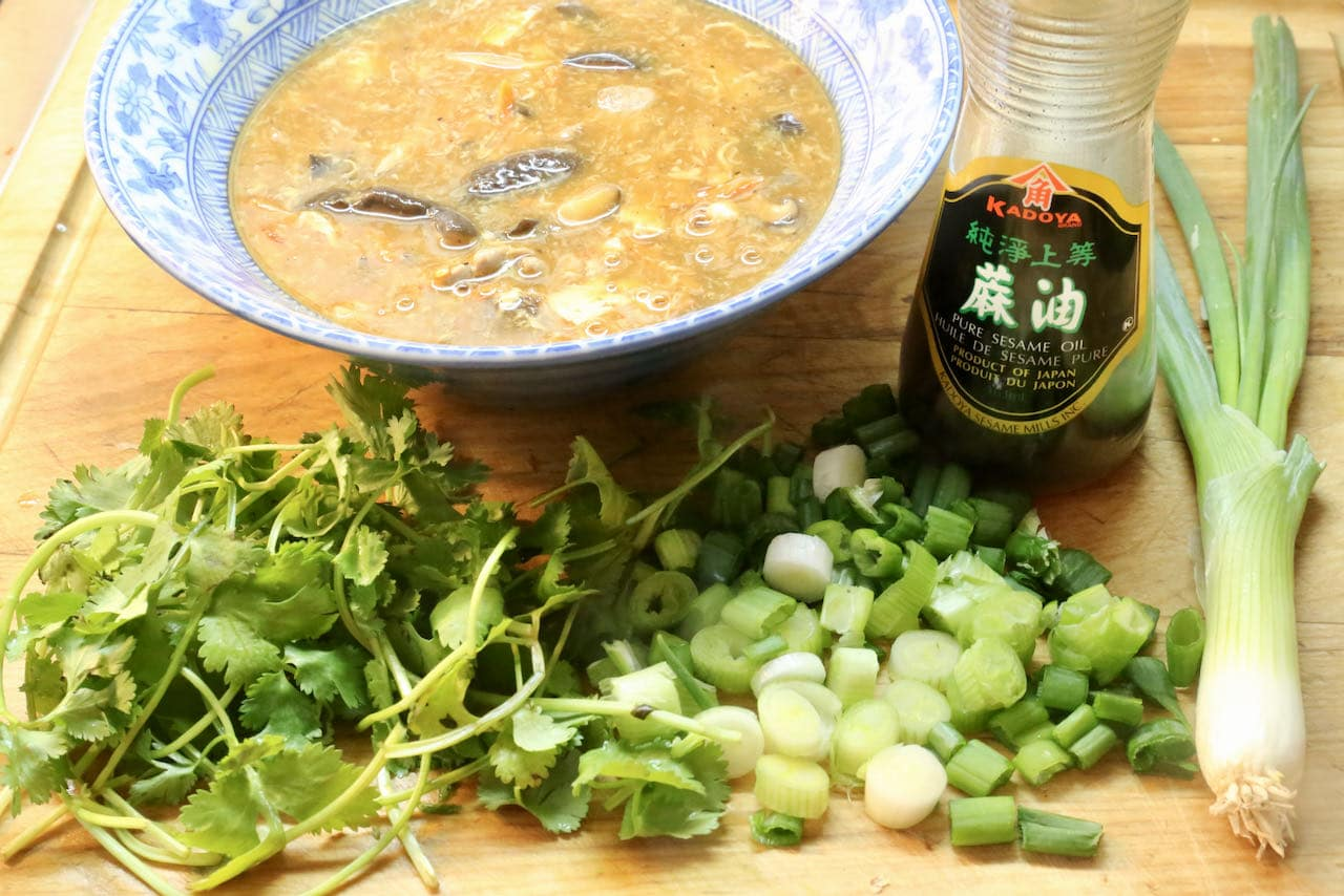 Garnish Szechuan Soup with sesame oil, scallions and cilantro.