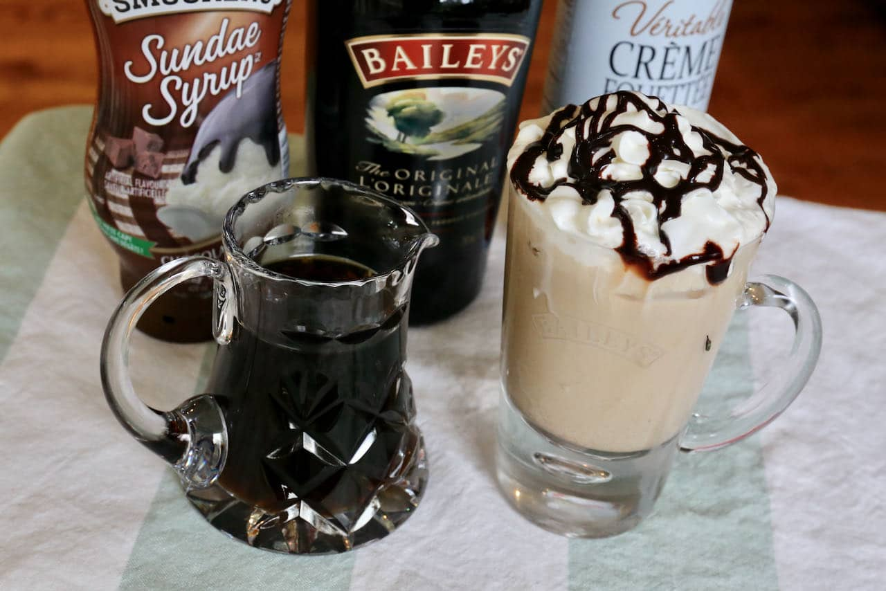 Baileys Iced Coffee is prepared with cold brewed coffee and is topped with whipping cream and chocolate sauce.