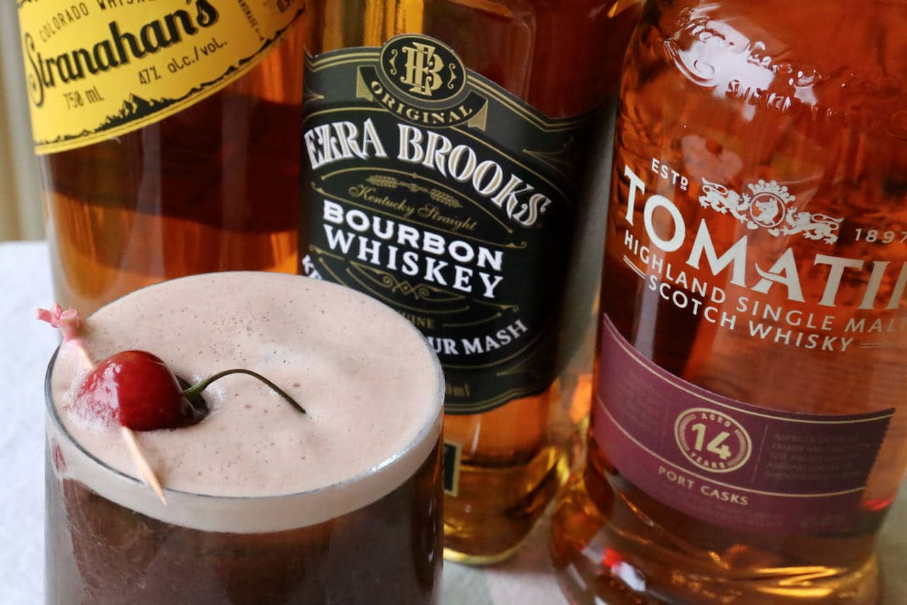 The cocktail features a frothy egg white foam, offering a creamy mouthfeel to this popular summer whiskey drink.