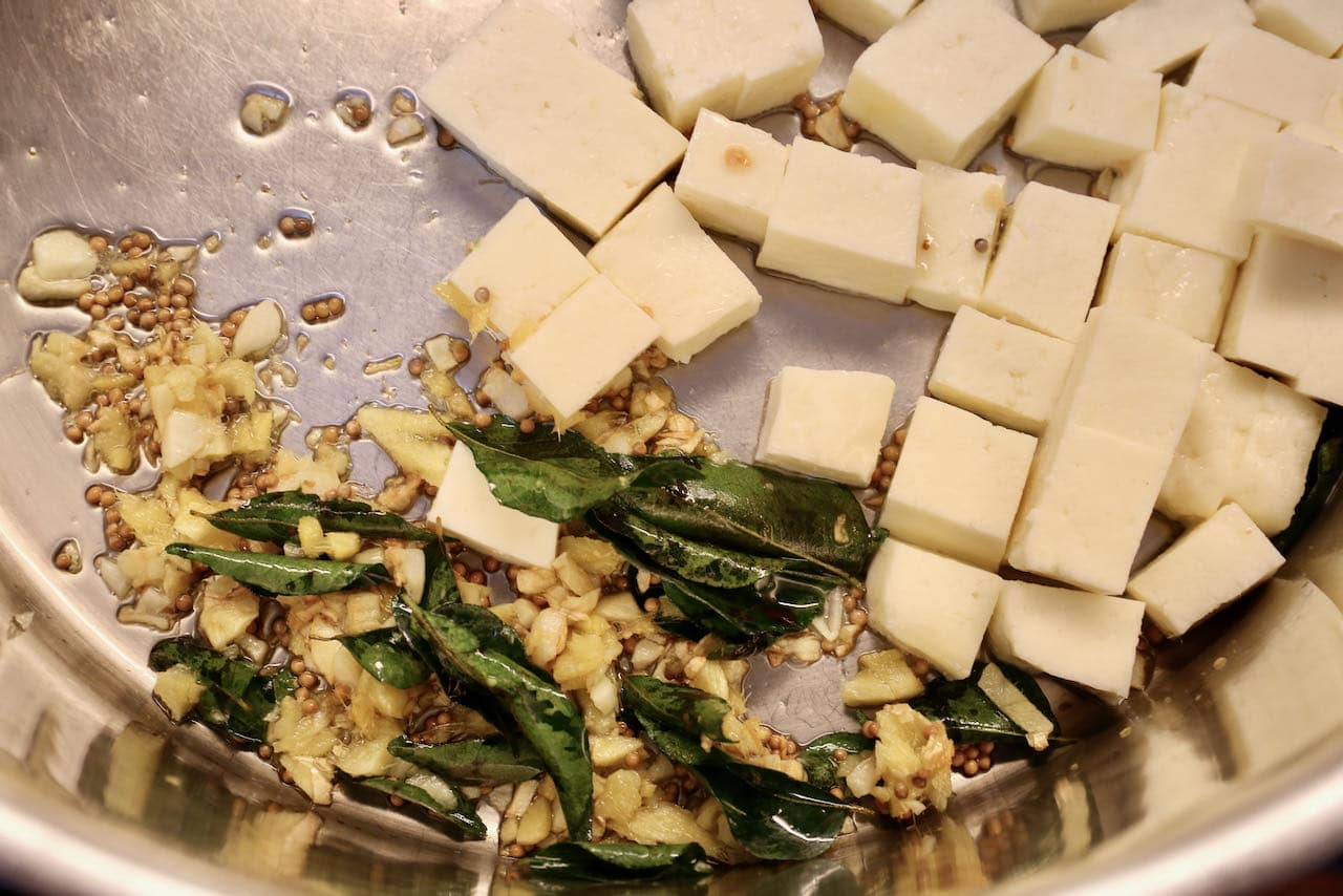 In a large pot fry oil, mustard seed, garlic, curry leaf and cubed paneer cheese.