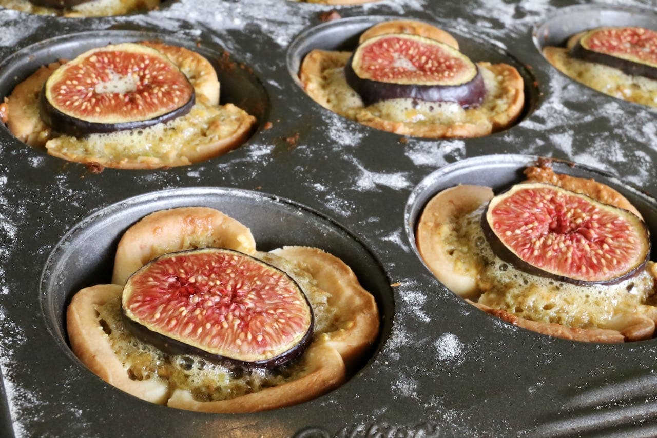 Top Pistachio Tartlets with slices of fresh fig.