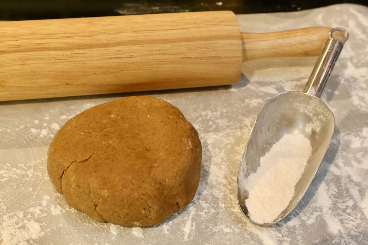 Roll chilled Gevulde Speculaas dough onto a lightly floured surface with a rolling pin.