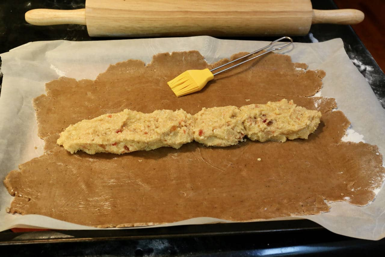 Wash Gevulde Speculaas dough with egg and create a log with almond cherry filling.