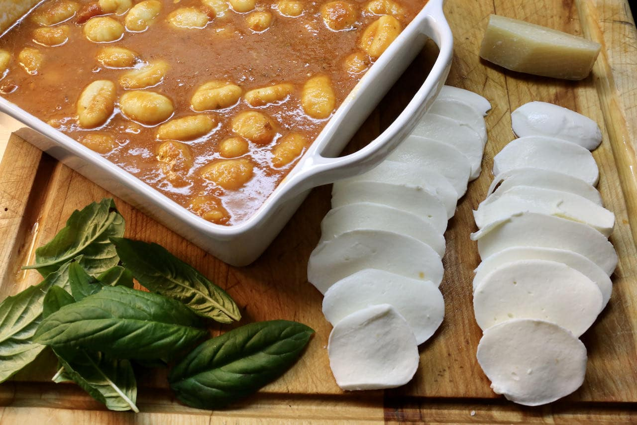 Assemble the gnocchi cheese bake in a casserole dish with cooked pasta, tomato sauce, mozzarella, parmesan and fresh basil.