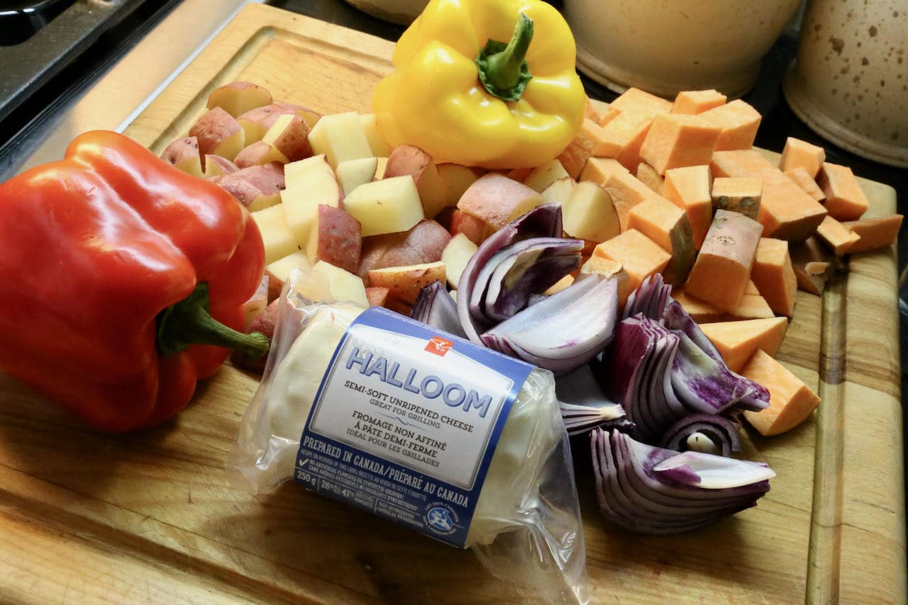 This healthy baked halloumi recipe features red onion, bell peppers, potatoes and sweet potatoes.