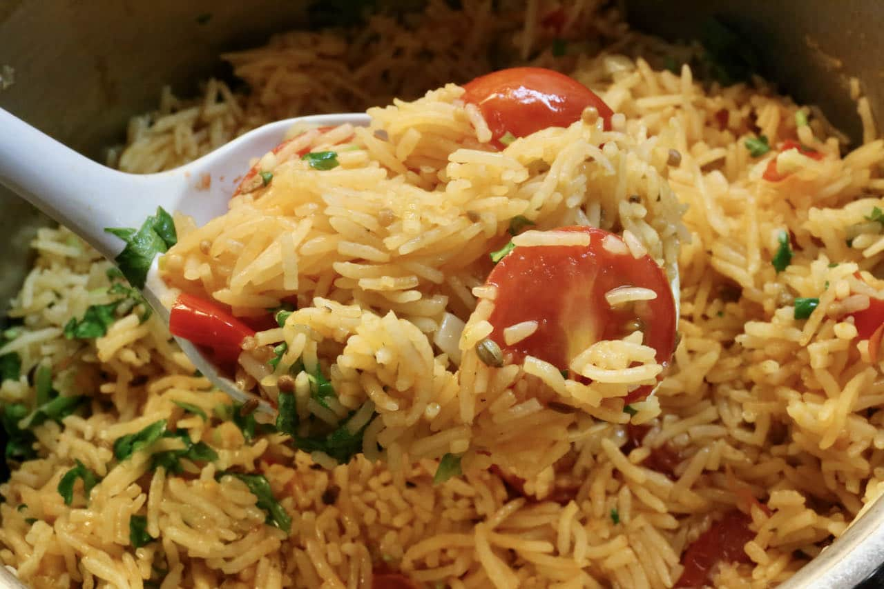 Scoop vegetarian Tomato Biryani into a large serving bowl as a side dish for an Indian feast.