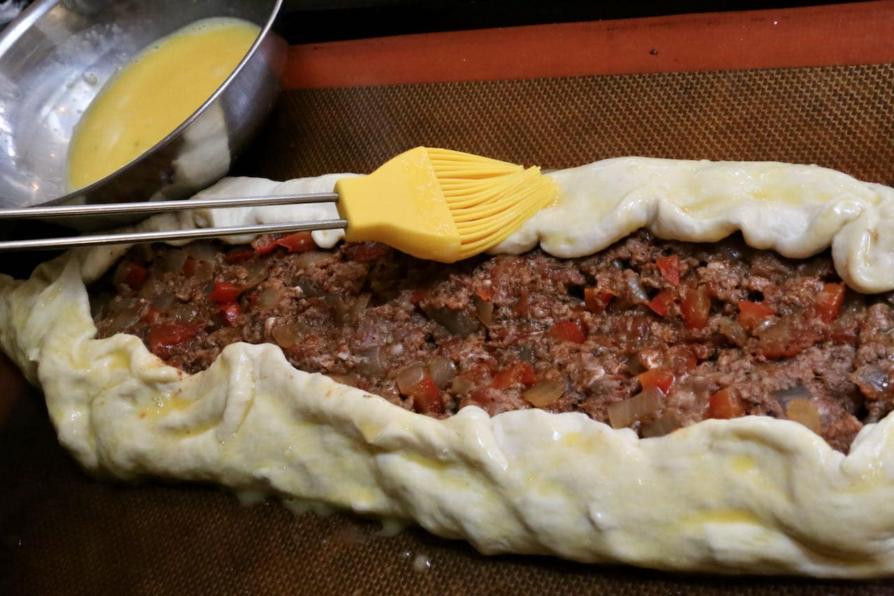 Paint Kiymali Pide crust with egg wash using a pastry brush.