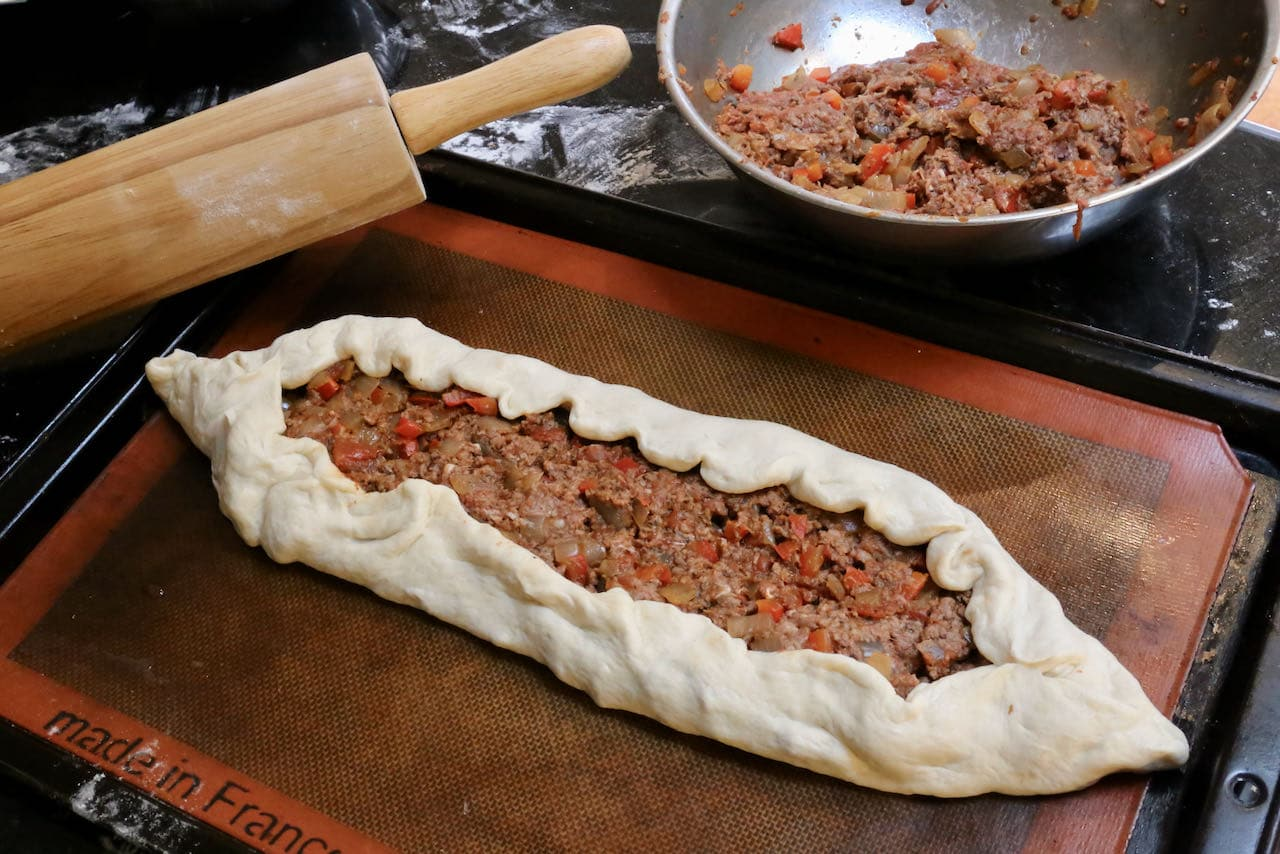 Use a rolling pin to roll out Kiymali Pide dough into an oval shape and fill with minced beef filling.
