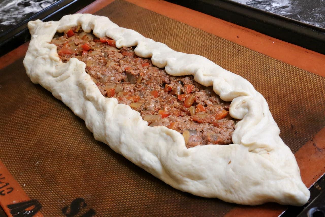 Fold Kiymali Pide dough inwards to create a 1-inch crust.