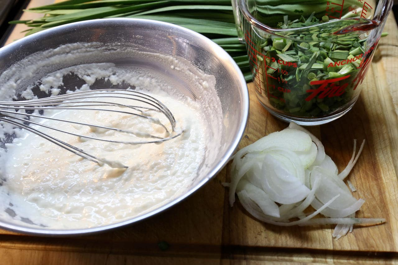 Prepare the Chive Pancakes batter in a mixing bowl and slice the vegetables.